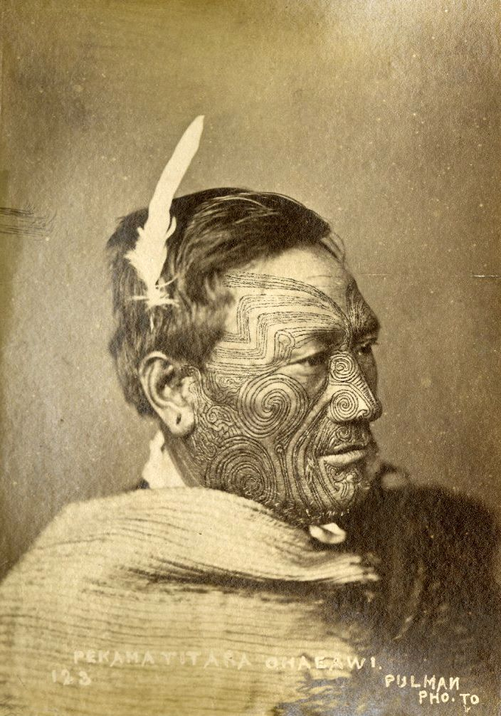New Zealand | Head and shoulders portrait of Maori man, Pekama Titara; wearing a white feather in his hair, kaitaka (finely woven flax cloak); with facial moko (tattoo) | Late 19th century | Photographed by Pulman