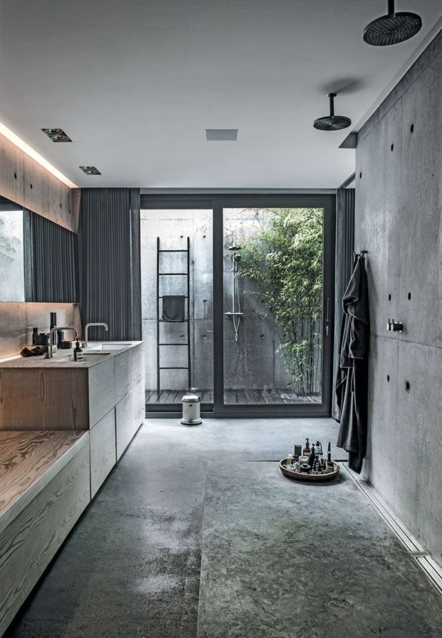 Concrete and timber bathroom with both indoor and outdoor shower.  The Design…