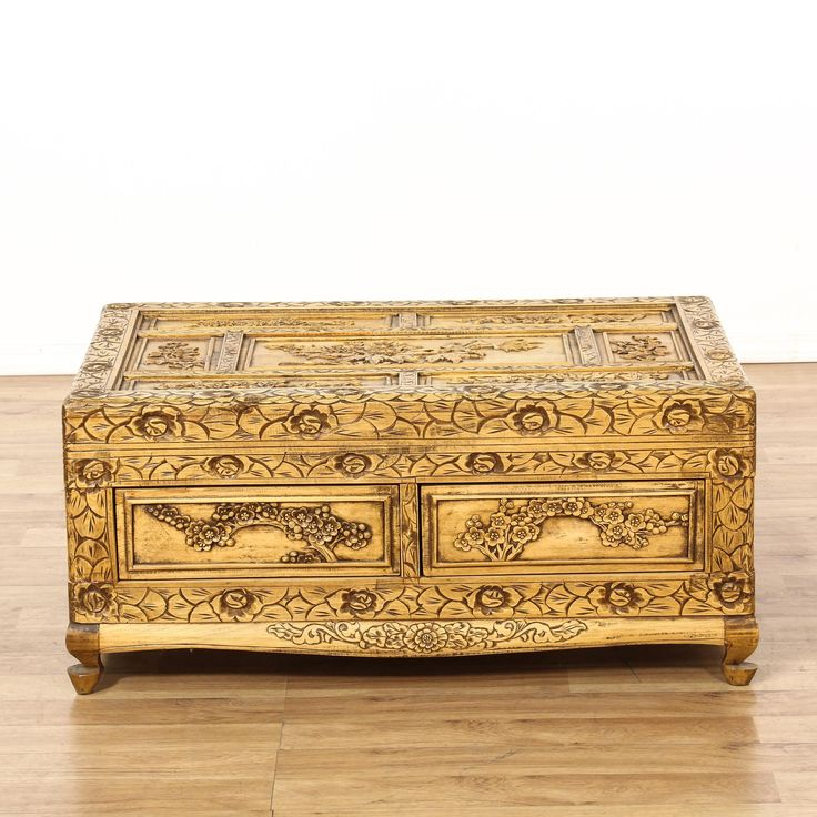 This coffee table is featured in a solid camphor wood with a glossy finish. This Asian-style cocktail table has 2 spacious drawers, intricately carved panels, and all-over bird and floral motifs. A stunning piece that's perfect for any home! #asian #tables #coffeetable #sandiegovintage #vintagefurniture