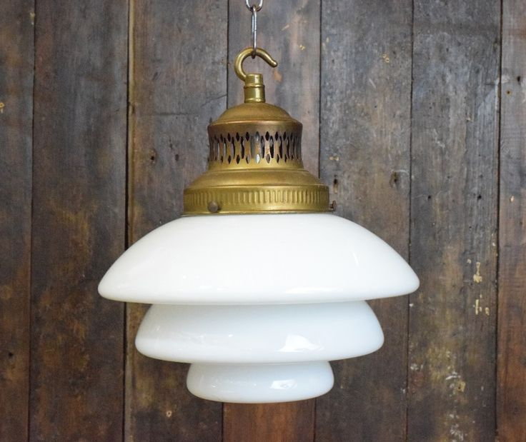 Beautifully proportioned small to medium sized genuine Art Deco Tiered White Opaline Glass Pendant Light with original aged brass gallery. Beautiful glossy white opaline glass with a nicely detailed brass gallery. Note that the underside of the shade is fully enclosed – not open. Size – 23cm diameter. Height from bottom of shade to top of gallery hook 26cm. Height of shade 15cm. Lights will be wired to custome...