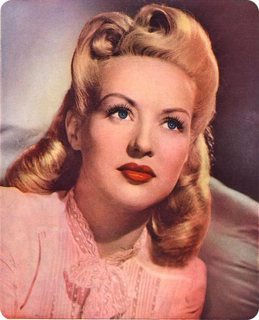 Betty Grable studio portrait; b & w photo that's been hand-painted.