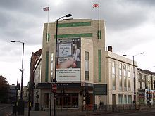 A large cream-coloured and tiled building stands at the intersection of two roads. Dark grey clouds dominate an overcast sky. Two flags are flying from the fascia of the building, which is covered mostly by a large advertising hoarding.