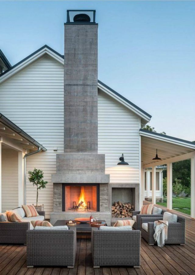 Modern farmhouse patio deck with outdoor fireplace and wicker seating set.