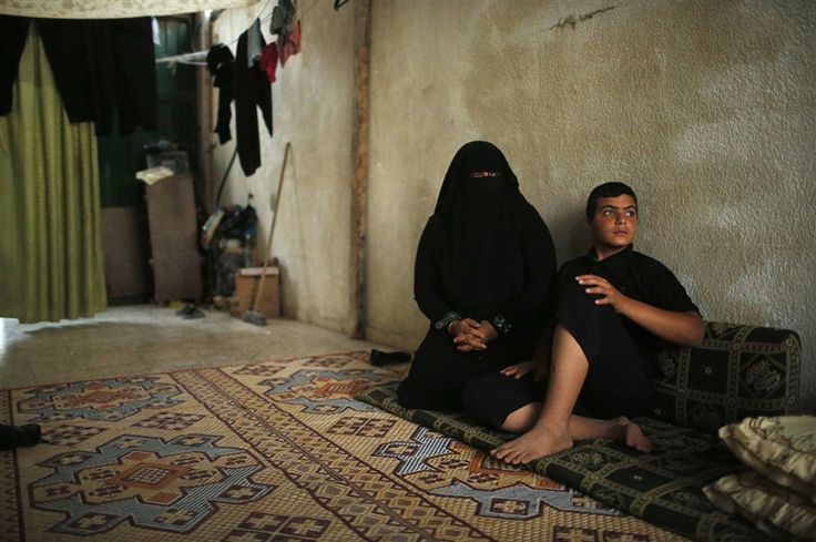 Palestinian boy Mahmoud Haniyeh, 13, sits with his mother, Umm Mohammed, left, at his family's house after returning from a summer camp organized by the Hamas movement, in Gaza City on June 16.