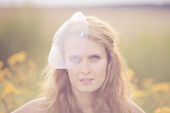 This cocktail hat has a fine hand-sewn crinoline veil with flufffy spots that covers a small part of the face diagonally as a blusher. The sinamay