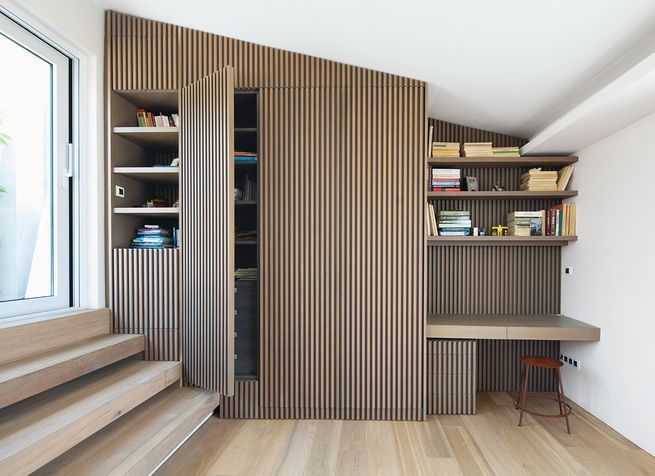 This family in Athens, Greece, converted wasted space on a landing into a utiliarian home office with the help of built-in shelving and bookcases fronted in vertical strips of oak.  Photo by: Gunnar Knechtel