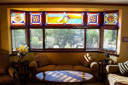 Wood blinds combined with stained glass add a twist to this Bay Window.