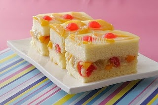 Crema De Fruta - recipe -Ingredients    CAKE  6 eggs,   3/4 cup white sugar,   1 1/4 cups cake flour,   1 teaspoon ground nutmeg,   1/4 teaspoon salt,   1/4 cup butter melted,      FILLING ---  1 cup white sugar,   1/3 cup cake flour,  2 3/4 cups milk,  5 egg yolks,  3/4 cup water,  1 teaspoon vanilla extract,   - TOPPING-   1 (15.25 ounce) can fruit cocktail, drained and juice reserved  2 tablespoons unflavored gelatin