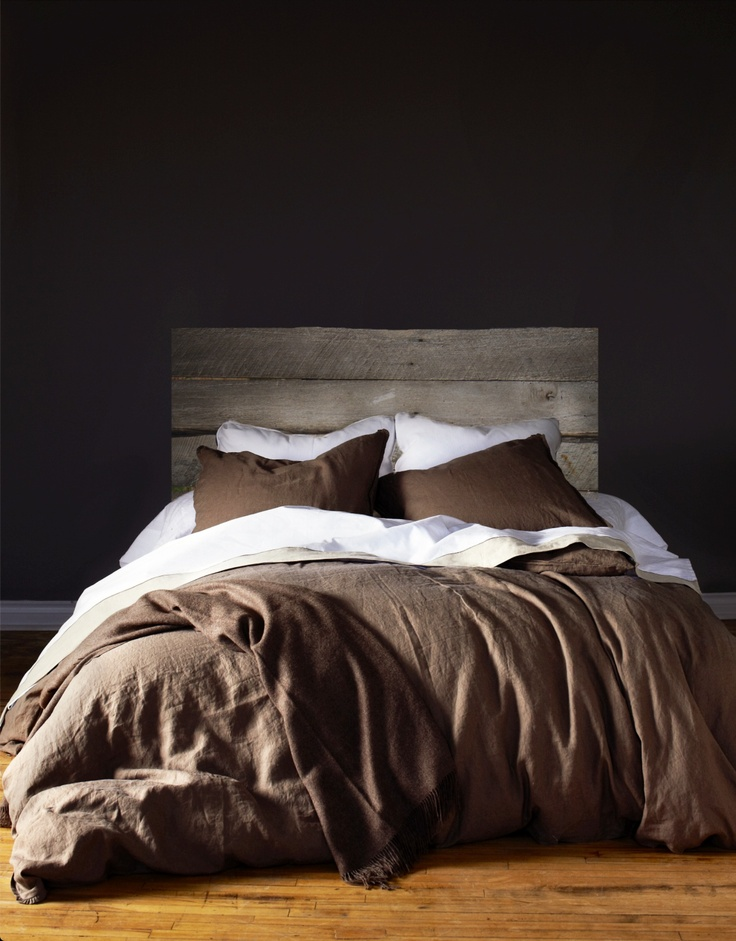 Just add candles for bliss. Dark wall, rustic wood headboard, wood floors, lush linens.