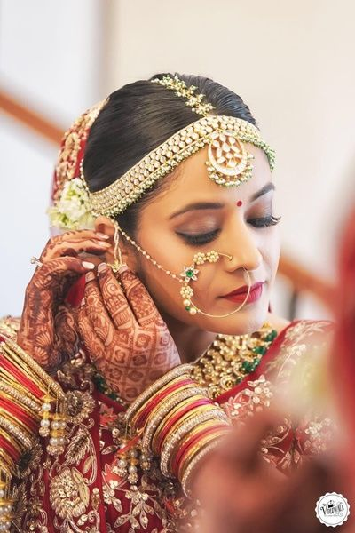 indian Wedding Jewelry - Bride in a Gold and Emerald Nath and a Gold Maang Tikka | WedMeGood #wedmegood #indianbride #indianwedding #bridal #mathapatti #nath