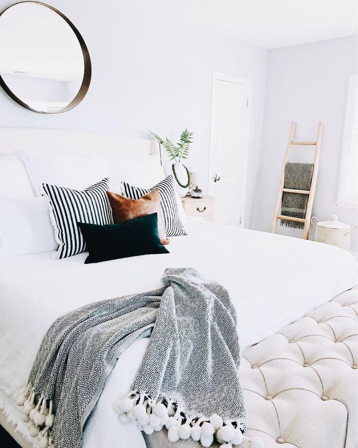 White light bedroom. Circle mirror, ladder blanket, tuffed bench, pillows