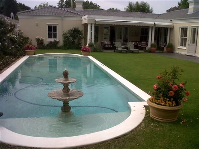 Charming villa minutes walk from Constantia Village. 4 lovely sunny bedrooms. 3 overlook the swimming pool. Large well kept gardens. 2 lounge area, open plan kitchen area. The main bedrooms has a separate walk in cupboard and en suite bathroom. Secure gated complex.