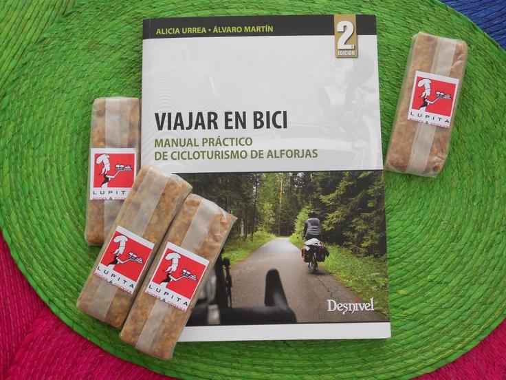"""""""Viajar en bici. Manual práctico de cicloturismo de alforjas"""", con barritas energéticas de dátiles y naranja."""