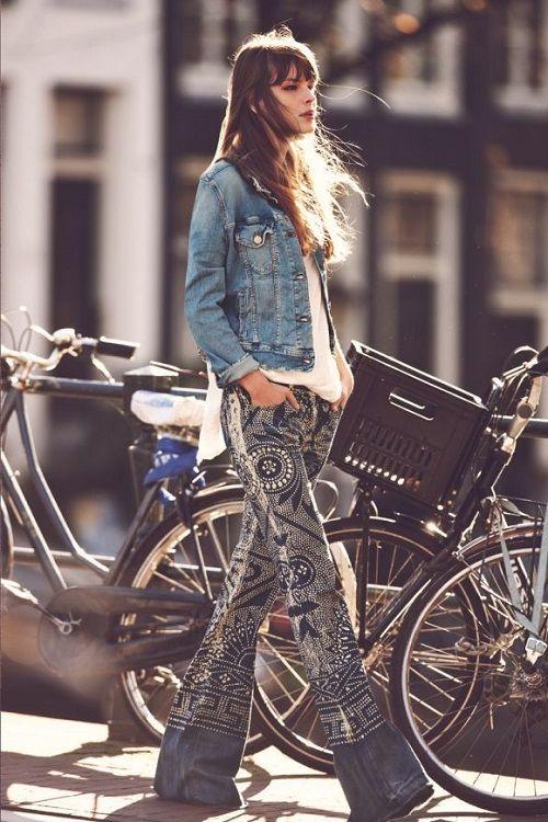 Девушка в, рассшитых джинсах клеш, и джинсовой куртке и дет по улице - стиль хиппи