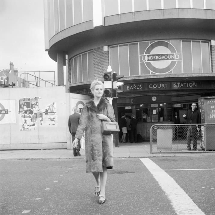 26th August 1966: Actress Louise Thompson crossing the road outside Earls Court underground station, London, with a portable radio covered in ponyskin to match her fur coat.
