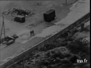"""Construction du mur de Berlin; en francais; le 13 août 1961, des allemands sont interrogés le long de la Bernauer Straße - ils font signes à des membres de leurs familles, restés/""""enfermés"""" à Berlin Ouest."""