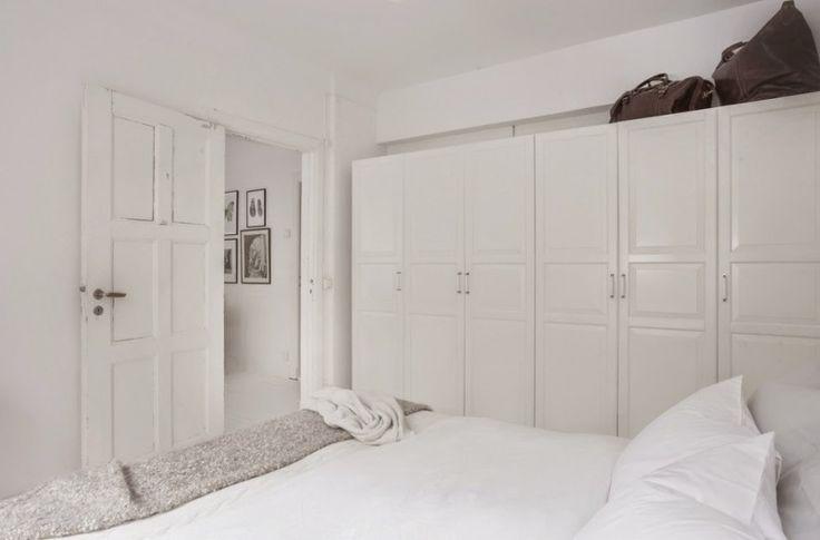 W sypialni ustawiono pojemne białe szafy wzdłuż jednej ściany. Śnieżna paleta barw wprowadza nieco chłodny nastrój, a...