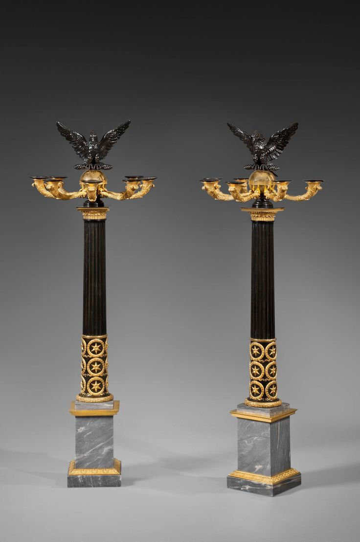 """A Rare Pair of Empire Seven Light Candelabra, Paris, circa 1810 - Patinated and gilt bronze, """"bleu Turquin"""" marble - The central part of the shaft is a patinated bronze fluted column, the lower part being adorned with gilt bronze stars within ribonned wreaths between a plain molding and a ribonned wreath and the upper part with a composite capital with eggs-and-darts, stiff leaves and water leaves. The shaft is topped by a patinated bronze open winged eagle - Dim: Height: 138 cm (54 ¼ in.)"""