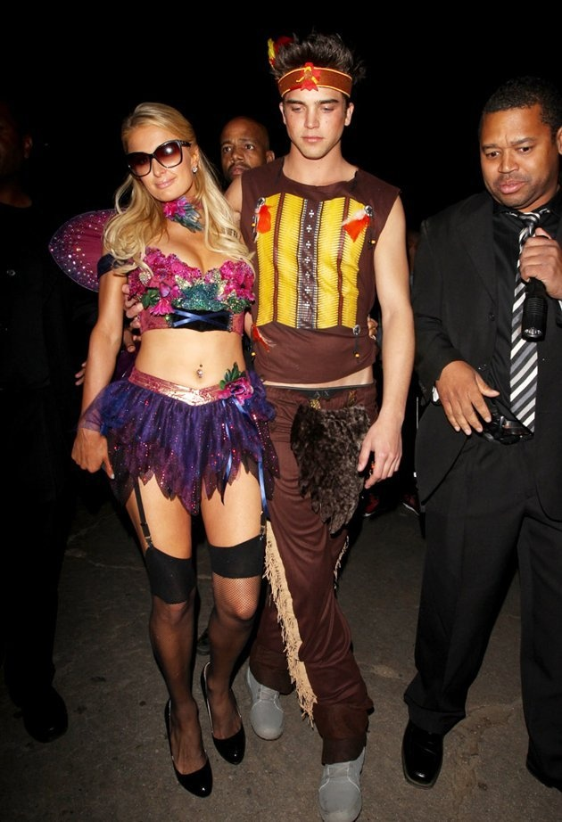 """Paris Hilton sported a skimpy fairy outfit while her boyfriend River Viiperi dressed as an Indian for the party at the Playboy Mansion. The costumes were their second of the weekend since they dressed as Alice from """"Alice in Wonderland"""" and the Mad Hatter on Friday for a private bash in Beverly Hills."""