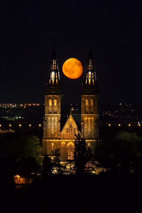 The moon rising between the spires of Vysehrad Church in Prague, Czech Republic
