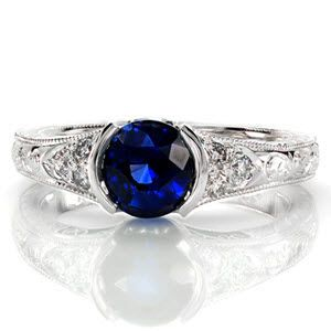 Sapphire Seville displays a 1.25 carat vibrant blue gemstone. The high polished half-bezel fashions the vivid round sapphire. A cluster of three diamonds flank each side the center stone. Hand engraved patterns and milgrain adorn this antique inspired ring for a picturesque view.