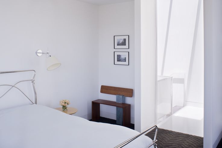 Back in the master bedroom, the designers installed Tolomeo wall sconces by Artemide next to the bed and placed a bench next to the door made by Hart's uncle, Peter Czuk of Czuk Studio. The bedroom door, which is rarely closed, is the starting point for the continuous flow of movement and light from the top of the house to the main level and down to the bottom floor.  Photo by   Sharon Risedorph