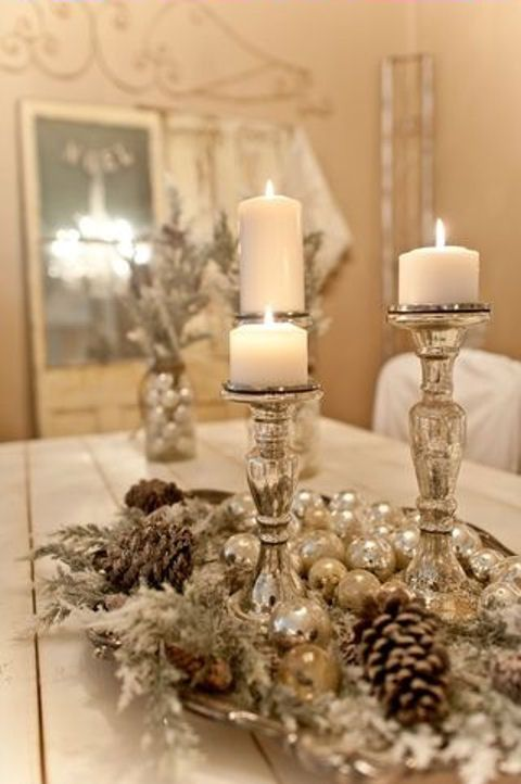 Christmas dining table center piece--silver tray lined with flocked greenery and pinecones, three silver candlesticks and white pillar candles, interspersed with small silver ornaments.: