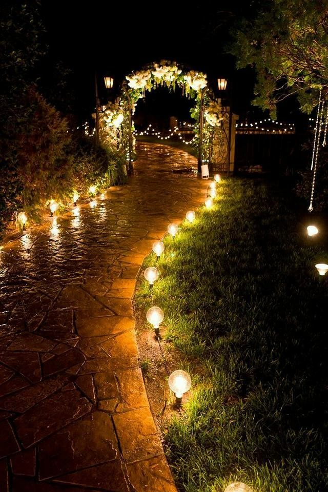 party lighting ideas. cafe bulbs light the path to a decorated arch at this outdoor evening wedding reception party lighting ideas
