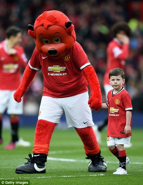 Kai Rooney joins Fred the Red as United's mascot for the day.