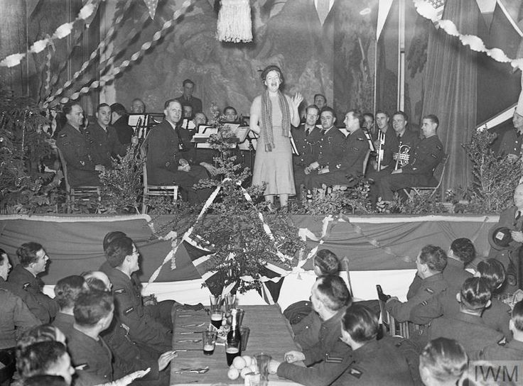 Gracie Fields, accompanied by an RAF orchestra, entertains airmen at their Christmas party.