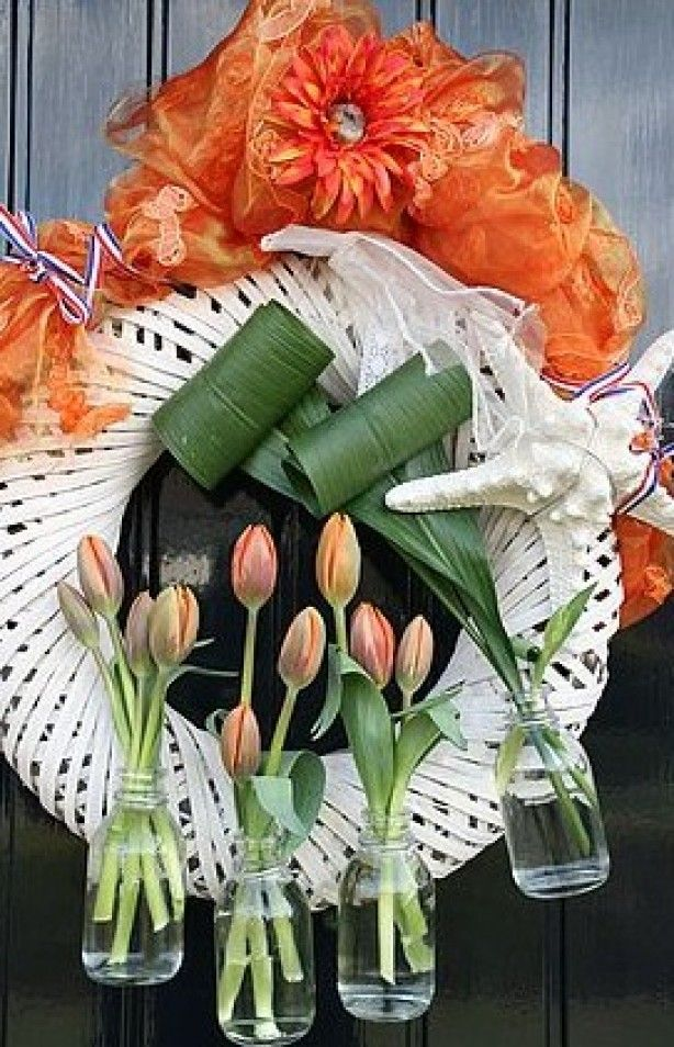 Krans voor Koninginnedag / Koningsdag / Kroningsdag Nodig: krans, oranje voile, witte voile/ kant, rood-wit-blauw lint, oranje tulpen, aspidistra blad, schelp/zeester, flesjes, binddraad, oranje zijdebloem.