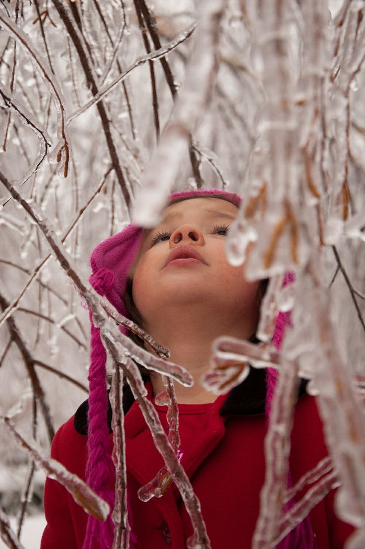 little girl in red in ice laden tree from ice storm
