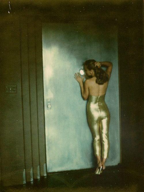 Model wearing a gold jumpsuit, Paris, 1970s.  Photo by Helmut Newton.