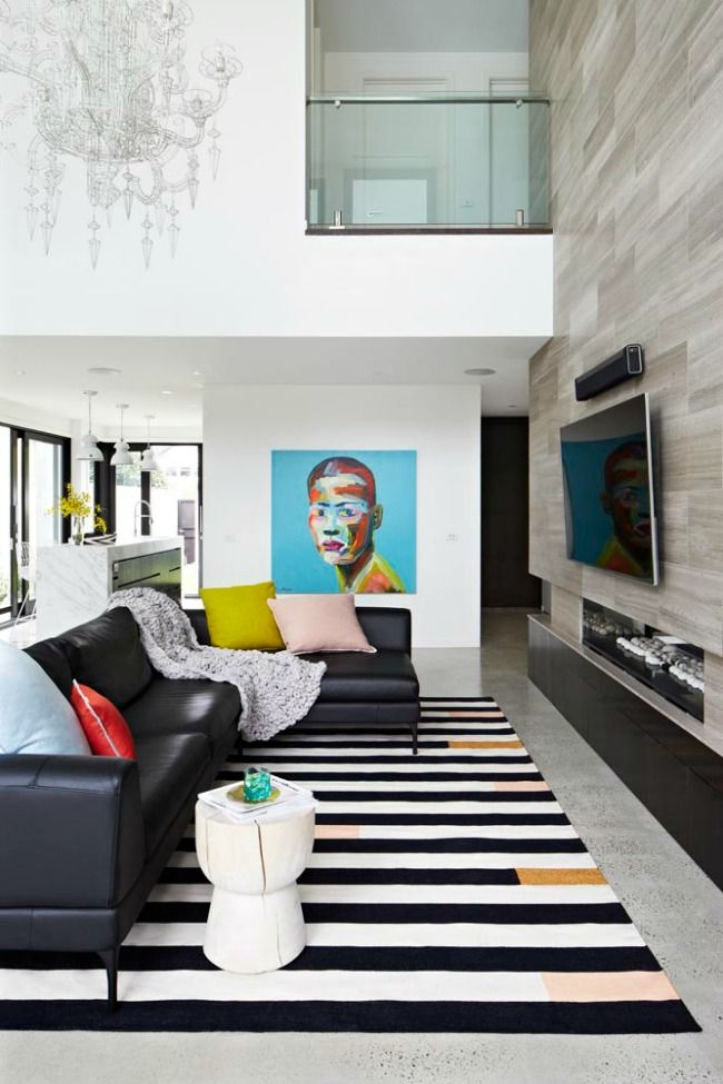 Open living space with minimalistic neutral color furniture pieces but adding splashes of color through decor