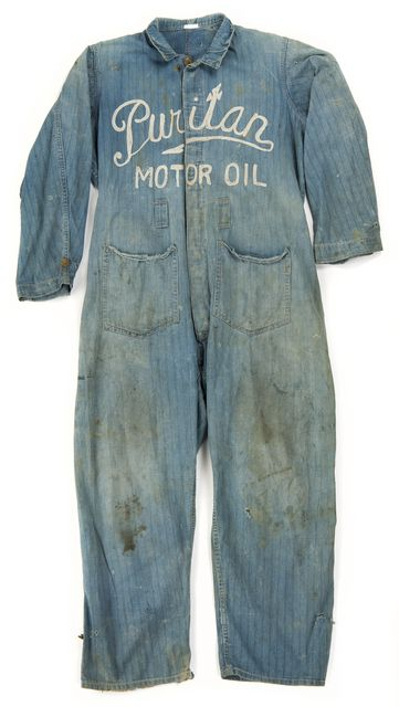 Puritan Oil Company coverall, 1915. Blue denim one piece work coverall with 'Puritan/Motor Oil' chain stitch embroidered across front. ID # 2005.137.1. Minnesota Historical Society.