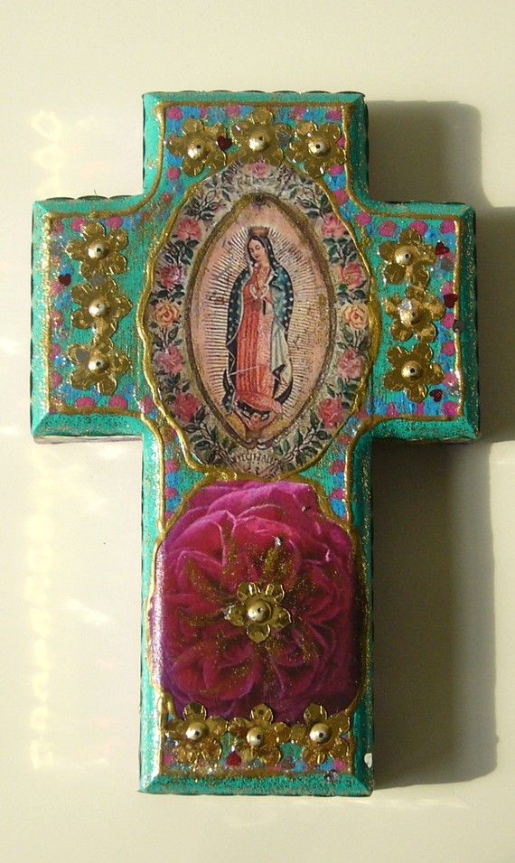 Wooden cross painted turquoise, gold, pink and blue.  Our Lady of Guadalupe, pink rose and sequin stars. Madeline Stevens.