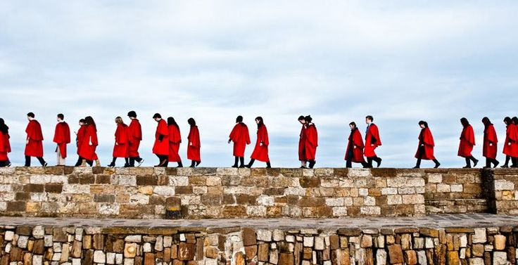 St Andrews University students taking part in the Pier Walk in their red academic gowns