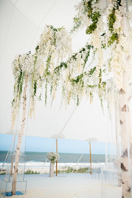 A pretty beach wedding ceremony decorated with birch poles white flowers and ghost chairs