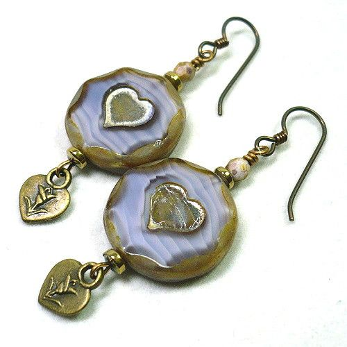 Distinctive heart themed earrings pair rustic bronze shades with the soft lilac to reflect a simple sophistication in these dangle earrings.  The silhouette of the Czech glass beads are so charming and reflect the ingenuity that goes into the creation of these unique glass beads.  These Czech glass gold-washed lilac beads are produced in layers, and then carefully polished to bring forth the shades underneath.  These beads are round with an octagon shape to the surface and a heart carved…