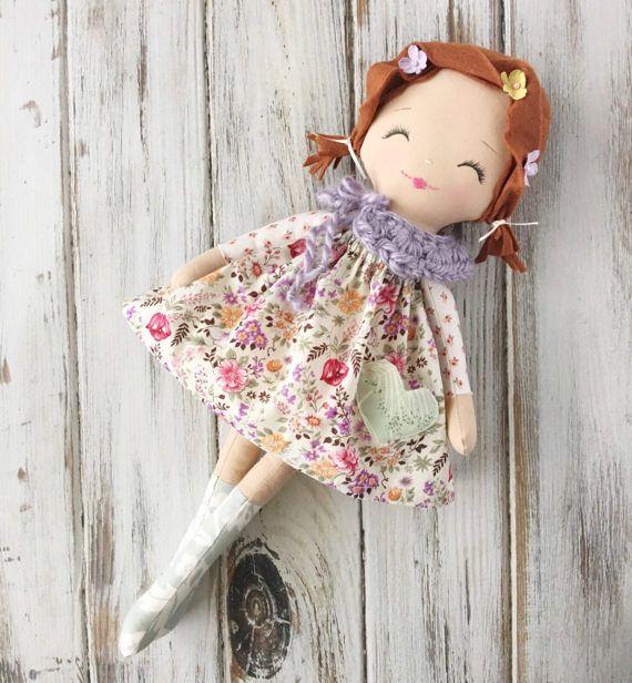 Cheveux de la poupée sont fabriqué à partir d'auburn en feutre de laine et sont coiffé en tresses ondulées agrémentés de fleurs douces.  Sa tenue se compose d'une adorable robe imprimée floral avec une poche en forme de coeur, une paire de culottes bouffantes, un chéri noué col et genou haut chou.  Son visage est cousu à la main et détaillée avec douce, sourire les yeux et les joues douces, roses.  Mesure environ 17 pouces de la tête aux pieds et vient joliment emballé et emballage cadeau…
