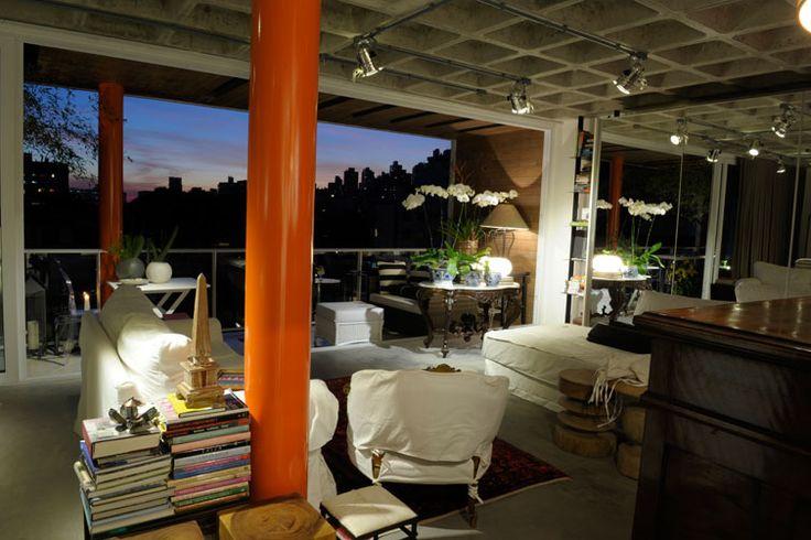 Com laje nervurada aparente e piso similar ao cimento queimado, projeto de interiores da designer Eda Fontoura integra visualmente todas as áreas do imóvel