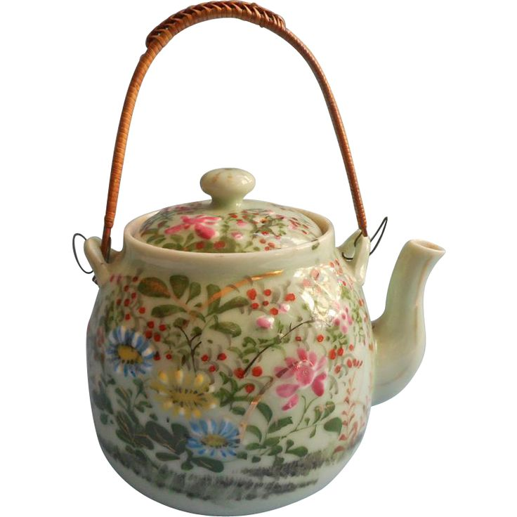 Very vintage to antique pottery teapot, celadon green ground with hand painted floral motifs on raised, molded body. Rattan over wire handle. The