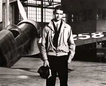 Howard Hughes poses next to the red H-I aircraft in which he set the trans-continental speed record in January 1937