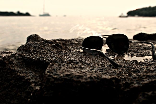 Selective Focus Stones & Water Sunglasses Sunset Vacation Time