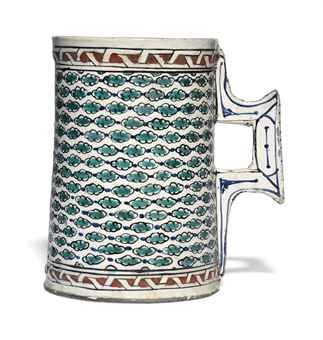 A LARGE IZNIK POTTERY TANKARD - OTTOMAN TURKEY, CIRCA 1580 - Of typical form with angular handle, the white ground decorated in turquoise, cobalt-blue and bole-red with repeating bands of small turquoise cloud motifs joined by cobalt-blue dots, bands of red and white strapwork above and below, the handle with cobalt-blue accents, 7½in. (19.2cm.) high; 4¾in. (12cm.) diam. at rim