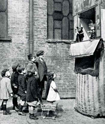 Children watching a Punch and Judy show on a London street in 1936 © The Print Collector