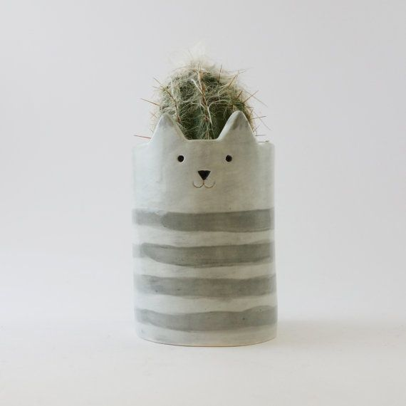 A grey cat planter or pen pot with a hand carved cat face. I hand build this pot…