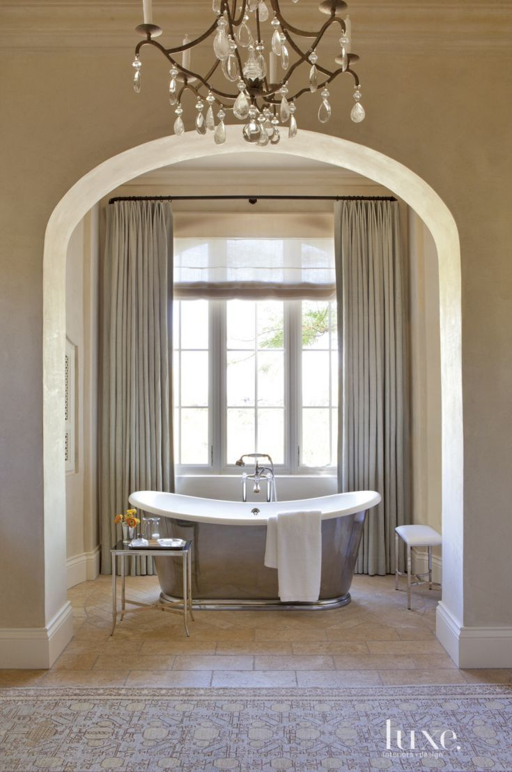 The water Monopoly's Cateau tub—with a Rohl tub filler from Clyde Hardware Co.—sports a pitted-pewter finish and provides a focal point in the master bathroom. The flooring is composed of rectangular antique-limestone pavers; the drapery fabric is by Rose Tarlow Melrose House.