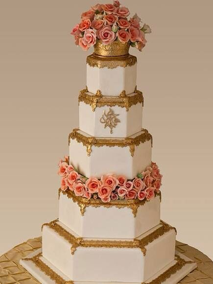 Multi-Teared hexagon shaped wedding cake with roses and gold trim