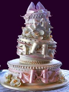 Artistic and creative three tier topsy turvy pink and white wedding cake decorated with intricate seams, bows and gum paste flowers.